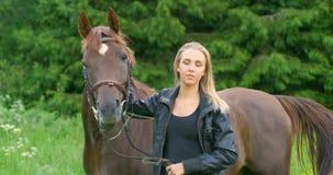 Giovane donna che accarezza il suo cavallo arabo che sta nel campo stock footage