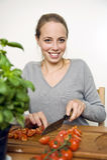Giovane donna che affetta i pomodori freschi Fotografia Stock