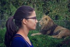 Giovane donna che affronta un leone Fotografie Stock