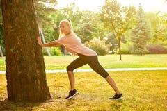 Giovane donna che allunga accanto ad un albero nel tramonto Fotografie Stock