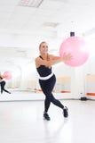 Giovane donna che allunga con il fitball all'allenamento dei pilates Fotografia Stock Libera da Diritti