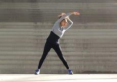 Giovane donna che allunga esercizio dei muscoli Fotografie Stock