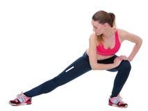 Giovane donna che allunga i muscoli della gamba Fotografia Stock Libera da Diritti