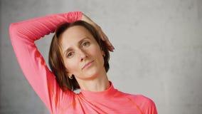 Giovane donna che allunga i muscoli irritati del collo mentre guarendo la macchina fotografica anteriore di massaggio Muscoli d'i archivi video