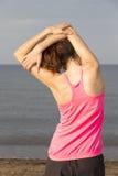 Giovane donna che allunga il tricipite sulla spiaggia Fotografie Stock