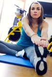 Giovane donna che allunga la sua gamba al riscaldamento nella palestra Fotografie Stock