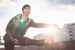 Giovane donna che allunga la sua gamba durante la routine scaldantesi all'aperto Fotografie Stock