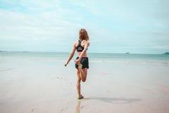 Giovane donna che allunga la sua gamba sulla spiaggia Fotografia Stock