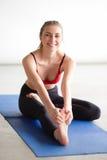 Giovane donna che allunga la sua gamba sulla stuoia di esercizio Immagini Stock Libere da Diritti