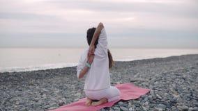 Giovane donna che allunga le mani che le tengono dietro la parte posteriore, sedentesi sulla costa del ciottolo stock footage
