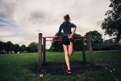 Giovane donna che allunga le sue gambe nel parco Immagine Stock Libera da Diritti