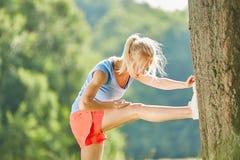 Giovane donna che allunga per l'allenamento Immagini Stock
