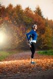 Giovane donna che allunga prima dell'correre nel prima serata in Th Fotografia Stock Libera da Diritti