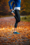 Giovane donna che allunga prima dell'correre nel prima serata in Th Immagini Stock