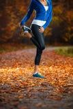 Giovane donna che allunga prima dell'correre nel prima serata in Th Fotografie Stock Libere da Diritti