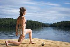 Giovane donna che allunga sul bacino del cedro Fotografia Stock