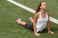 Giovane donna che allunga sul campo da giuoco Immagine Stock