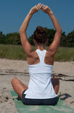 Giovane donna che allunga sulla spiaggia Fotografia Stock