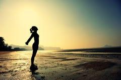Giovane donna che allunga sulla spiaggia di alba Immagini Stock Libere da Diritti