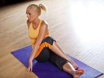 Giovane donna che allunga sulla stuoia di yoga Fotografia Stock Libera da Diritti