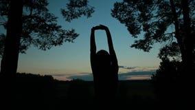 Giovane donna che allunga verso il cielo nella foresta dopo il tramonto stock footage