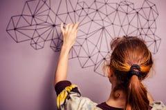 Giovane donna che appende un pezzo di arte sulla sua parete fotografie stock