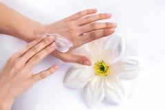 Giovane donna che applica crema sulle belle e mani manicured immagini stock libere da diritti