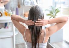 Giovane donna che applica maschera su capelli immagine stock libera da diritti