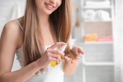 Giovane donna che applica olio su capelli immagini stock libere da diritti