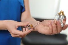 Giovane donna che applica profumo sul polso contro il fondo vago fotografie stock