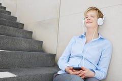 Giovane donna che ascolta la musica con le cuffie Fotografia Stock Libera da Diritti