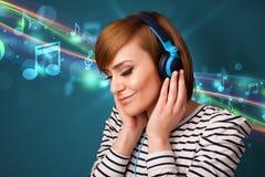 Giovane donna che ascolta la musica con le cuffie immagini stock libere da diritti