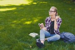 Giovane donna che ascolta la musica su erba all'aperto Fotografie Stock Libere da Diritti