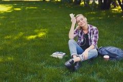Giovane donna che ascolta la musica su erba all'aperto Fotografia Stock