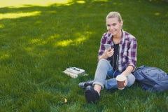 Giovane donna che ascolta la musica su erba all'aperto Fotografia Stock Libera da Diritti