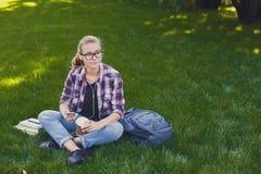 Giovane donna che ascolta la musica su erba all'aperto Immagine Stock Libera da Diritti