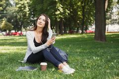 Giovane donna che ascolta la musica su erba all'aperto Immagini Stock