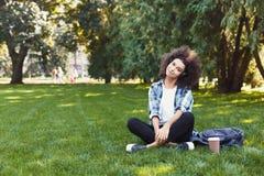 Giovane donna che ascolta la musica su erba all'aperto Immagine Stock