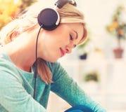 Giovane donna che ascolta la musica sulle cuffie fotografia stock libera da diritti