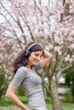 Giovane donna che ascolta la musica sulle cuffie senza fili in un parco con gli alberi del fiore di ciliegia immagine stock