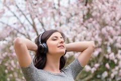 Giovane donna che ascolta la musica sulle cuffie senza fili in un parco con gli alberi del fiore di ciliegia fotografia stock libera da diritti