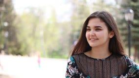 Giovane donna che aspetta una data del ragazzo dell'amico nel parco La ragazza attraente distoglie lo sguardo video d archivio