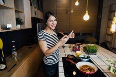 Giovane donna che assaggia un pasto sano in cucina domestica Facendo cena sulla fresa facente una pausa di induzione dell'isola d immagine stock