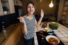 Giovane donna che assaggia un pasto sano in cucina domestica Facendo cena sulla fresa facente una pausa di induzione dell'isola d fotografia stock libera da diritti