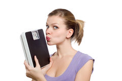 Giovane donna che bacia una scala del peso Fotografie Stock Libere da Diritti