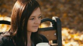 Giovane donna che beve caffè caldo nel parco di autunno stock footage