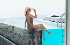 Giovane donna che beve un cocktail che gode di una vista magnifica di Santorini vicino allo stagno fotografie stock libere da diritti