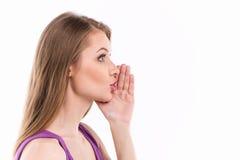 Giovane donna che bisbiglia sopra il fondo bianco Immagini Stock