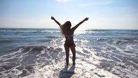 Giovane donna che cammina all'acqua di mare e che solleva mano Bella ragazza irriconoscibile che gode della vita e della libertà  video d archivio