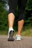 Giovane donna che cammina all'aperto nel parco da dietro immagine stock